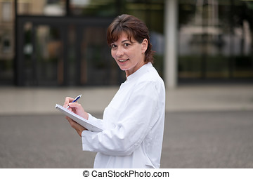 Smiling doctor or nurse taking notes