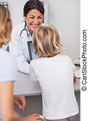 Smiling doctor presenting a tablet computer to a child