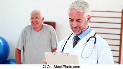 Smiling doctor reading from clipboard at the rehabilitation...