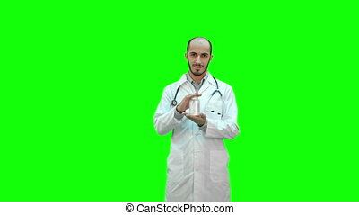 Smiling doctor recommending pills and showing a thumb up on a Green Screen, Chroma Key.