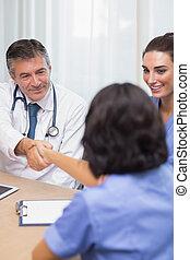 Smiling doctor shaking nurses hand