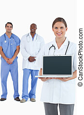 Smiling doctor showing laptop with colleagues behind her