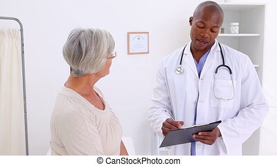 Smiling doctor talking with a mature woman