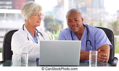 Smiling doctor talking with a nurse in front of a laptop in...