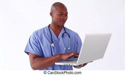 Smiling doctor using a laptop against a white background