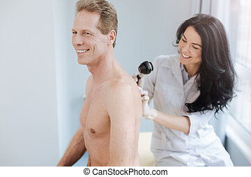 Smiling doctor using dermatoscope for skin problem examination in the clinic