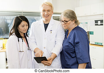 Smiling Doctor Using Digital Tablet With Team In Clinic