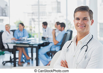Smiling doctor with arms folded standing