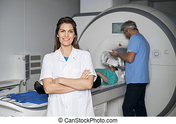 Smiling Doctor With Colleague Preparing Patient For CT Scan
