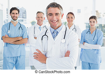 Smiling doctor with fellow doctors standing behind him