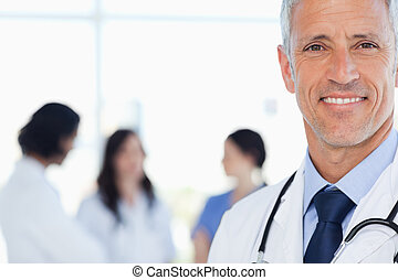Smiling doctor with his medical interns behind him - Doctor...