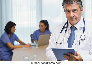 Smiling doctor with tablet