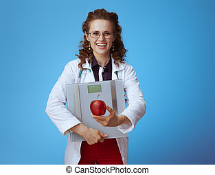 smiling doctor woman with weight scale showing apple on blue