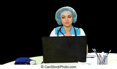 Smiling doctor working at the computer. Alpha channel.