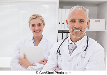 Smiling doctors coworker standing in medical office