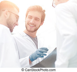 smiling doctors discussing x-ray with colleagues