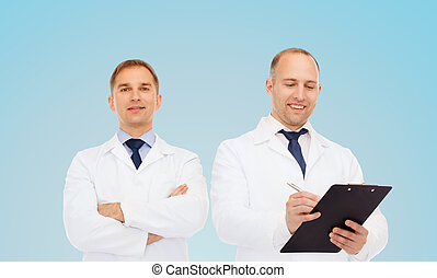 smiling doctors in white coats with clipboard