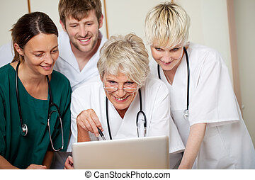 Smiling Doctors Looking At Laptop In Hospital