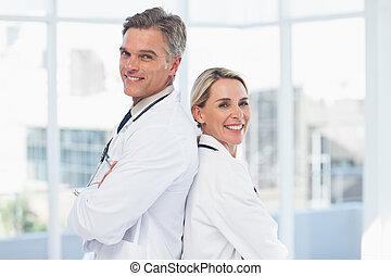 Smiling doctors posing together back to back