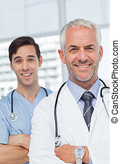 Smiling doctors with arms crossed looking at the camera