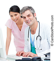 Smiling doctors working at a computer