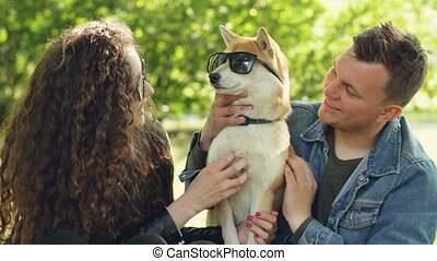 Smiling dog owners are patting puppy with sunglasses on its...