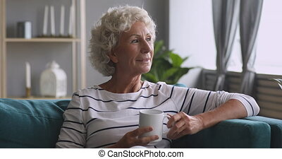 Smiling dreamy middle aged woman holding cup of hot coffee...