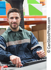 Smiling driver operating forklift machine