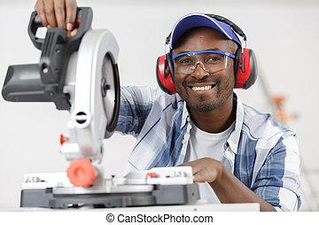 smiling efficient man wearing protective workwear operating circular saw