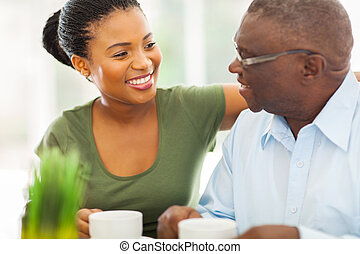 smiling elderly african american man enjoying coffee with...