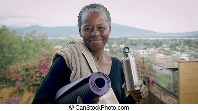Smiling elderly African American senior woman holding yoga...