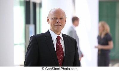 smiling elderly businessman with blurred team