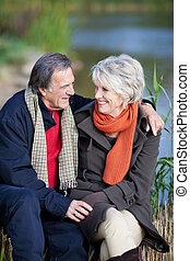 Smiling elderly couple on a lake shore