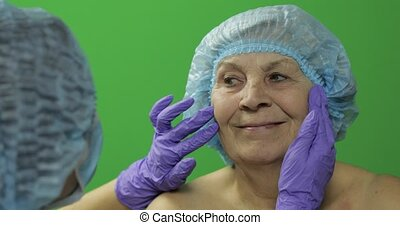 Smiling elderly female in protective hat. Plastic surgeon checking woman face