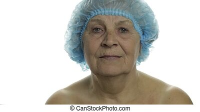 Smiling elderly female lady in protective hat scared of syringe with medicines