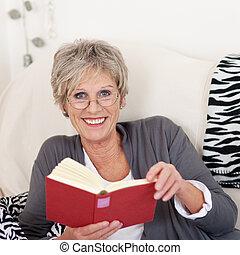 Smiling elderly female reading a book