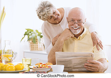 Smiling elderly man reading newspaper