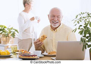 Smiling elderly man using laptop