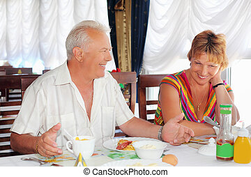 Smiling elderly married couple having breakfast at restaurant near window, Talk with each other