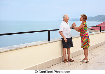 Smiling elderly married couple on veranda near seacoast, play handies