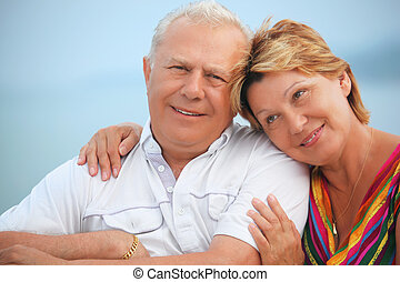 Smiling elderly married couple on veranda near seacoast, concerning with heads