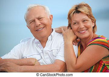 Smiling elderly married couple on veranda near seacoast