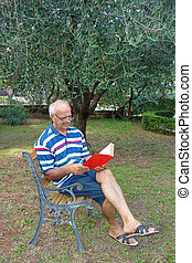 Smiling elderly pensioner having relax reading red book sitting on bench outdoor in the garden