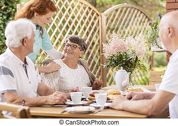 Smiling elderly woman and caregiver while eating breakfast with friends