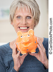 Smiling elderly woman holding a piggy bank