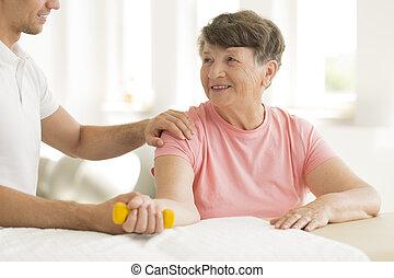 Smiling elderly woman holding dumbbell