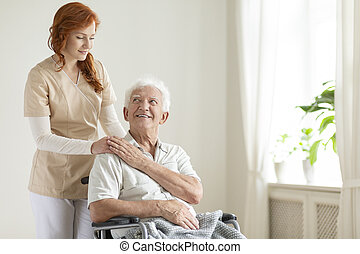 Smiling elderly woman in the wheelchair and friendly caregiver in a nursing house