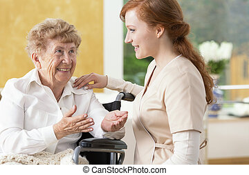Smiling elderly woman talking with friendly caregiver in the nursing house
