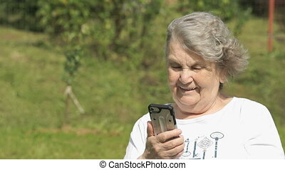 Smiling elderly woman talks using a smart phone