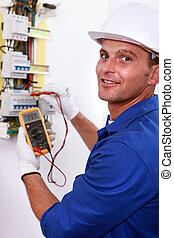 Smiling electrician using multimeter on electric meter